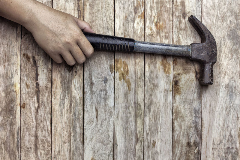 Cropped Hand Of Person Holding Hammer On Wooden Table