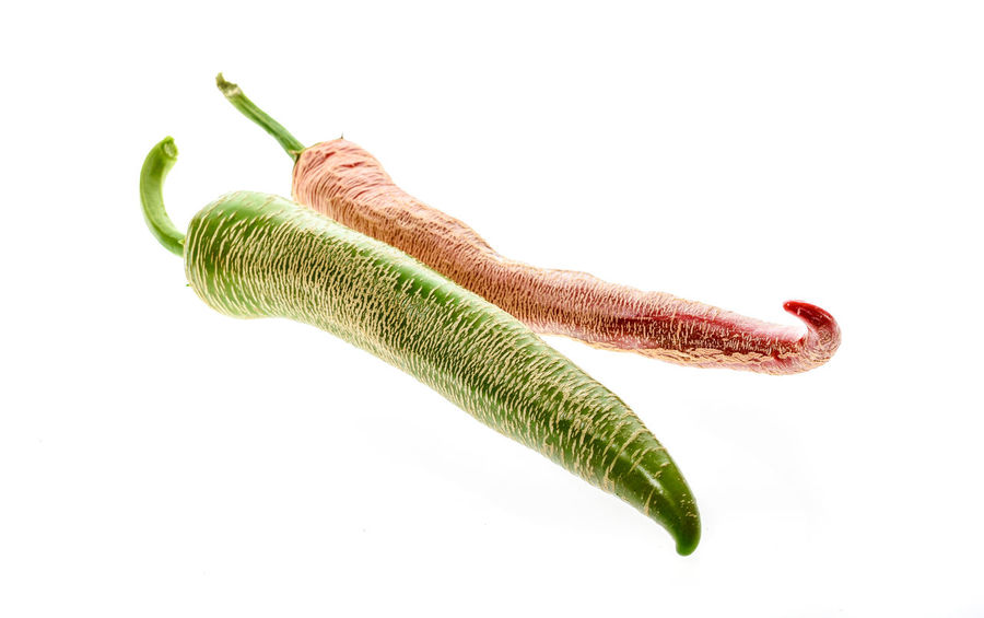 Organic Macedonian Fringed hot chili peppers with green stem. Studio image Isolated on white background. Capsicum Annuum Chili Pepper Green Hot Hot Pepper Macedonian Fringed Red Capsaicin Capsicum Chinense Capsicum Pepper Chilli Close-up Food Fresh Fringed Homegrown Jalapeno Pepper Macedonian Studio Shot Vegetable White Background