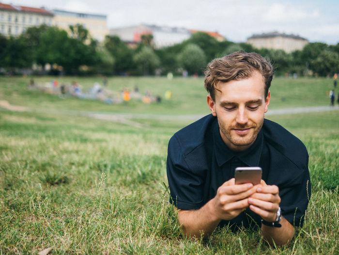 Mature man using smart phone on field