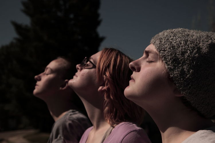 Sunlight Falling On Sisters With Eyes Closed During Solar Eclipse