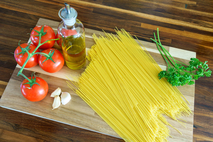 Preparing a pasta meal with tomatoes, garlic, olive oil, herbs. Food Food And Drink Freshness Garlic Healthy Eating Herb High Angle View Ingredient Italian Food No People Olive Oil Pasta Preparation  Spaghetti Spice Tomato Vegetable
