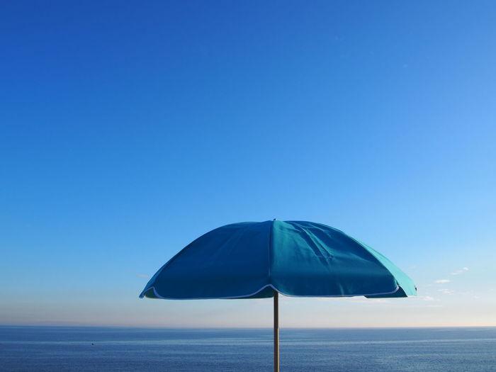 Parasol at beach against sky