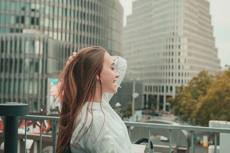 Side view of smiling young woman standing in city