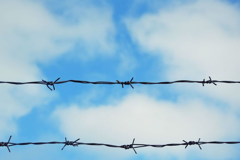Low angle view of barbed wires against cloudy sky