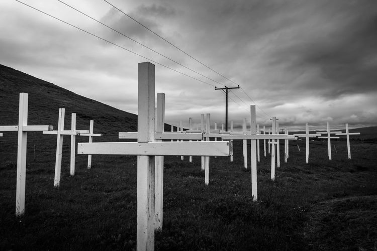 Cross Grave Graveyard Monochrone Black And White Sky Cloud - Sky No People Nature Environment Day Religion Architecture Spirituality Outdoors Field Belief Land In A Row Landscape Built Structure Boundary Fence Power Supply