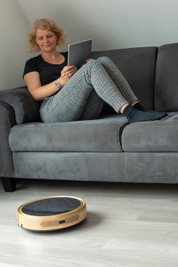 Woman holding digital tablet while sitting on sofa at home by vacuum cleaner