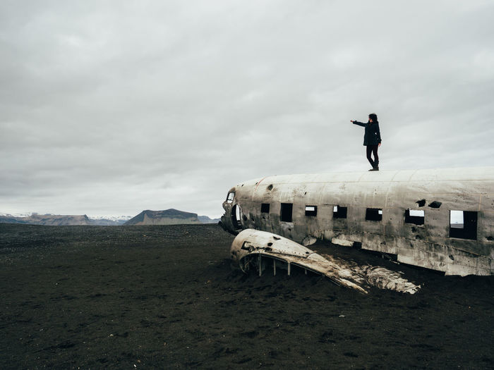 Man Standing On Airplane Wreck