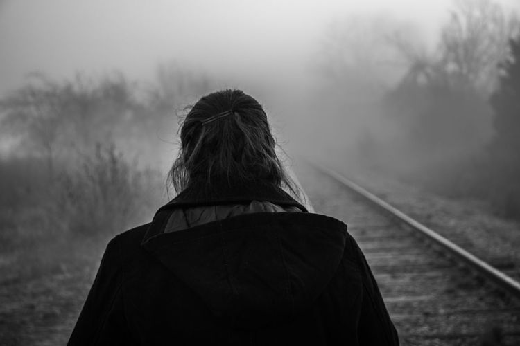 Rear view of person standing by railroad track