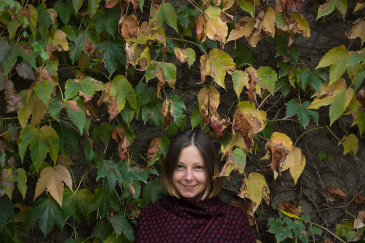 Portrait of smiling woman standing against leaves