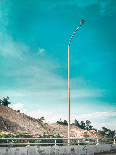 Street light by mountains against blue sky