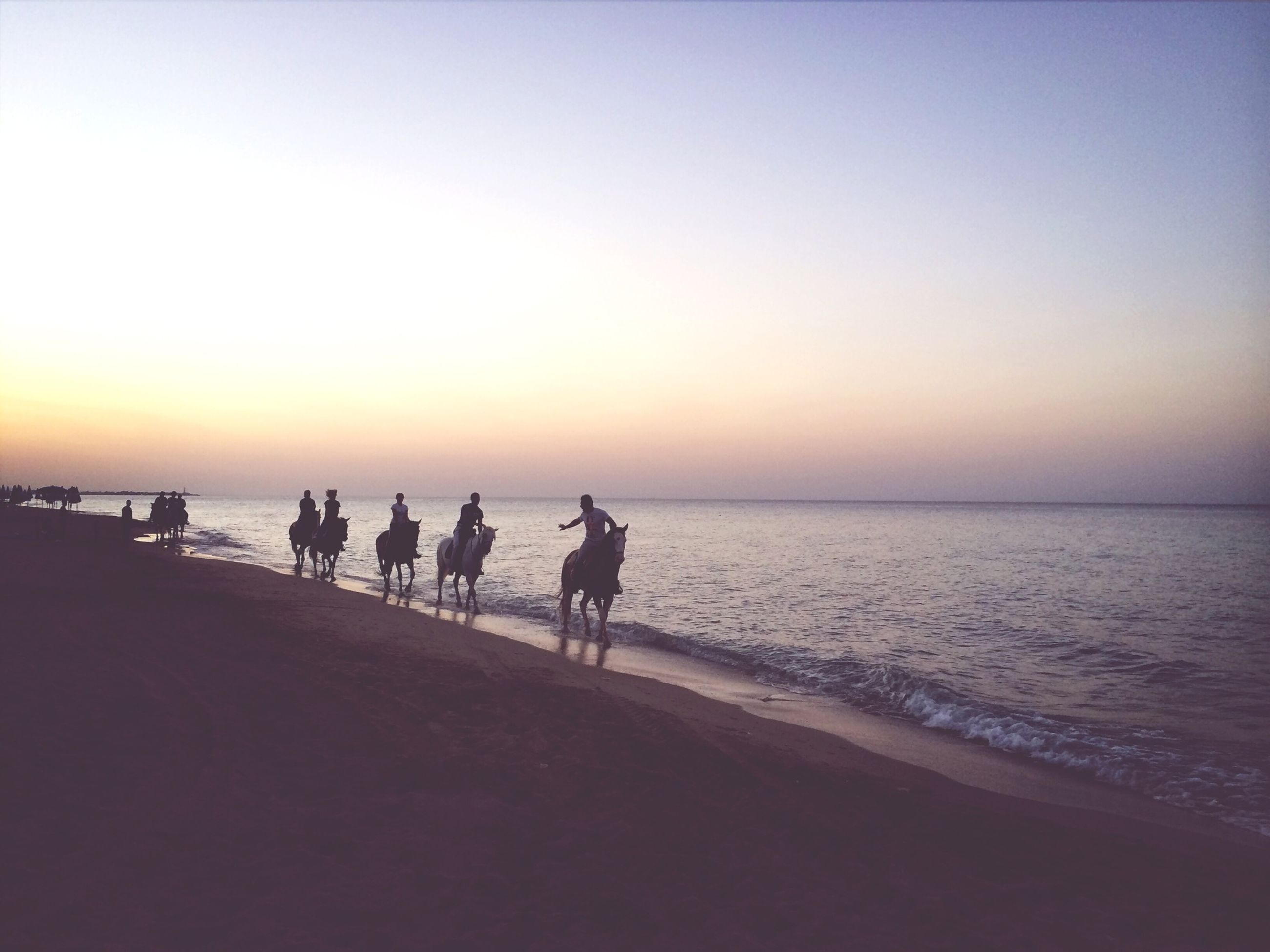 sea, sunset, horizon over water, water, beach, silhouette, copy space, clear sky, scenics, tranquil scene, men, tranquility, orange color, shore, leisure activity, beauty in nature, lifestyles, nature, walking