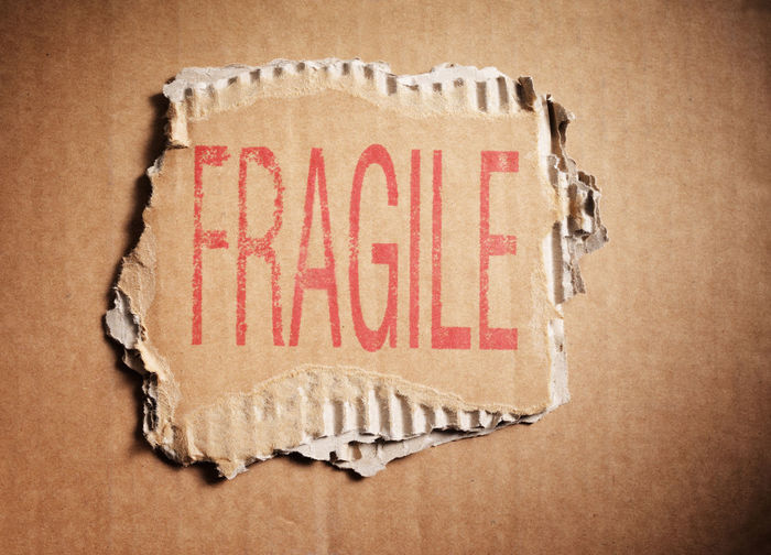 Word Fragile stamped on a piece of brown corrugated cardboard.