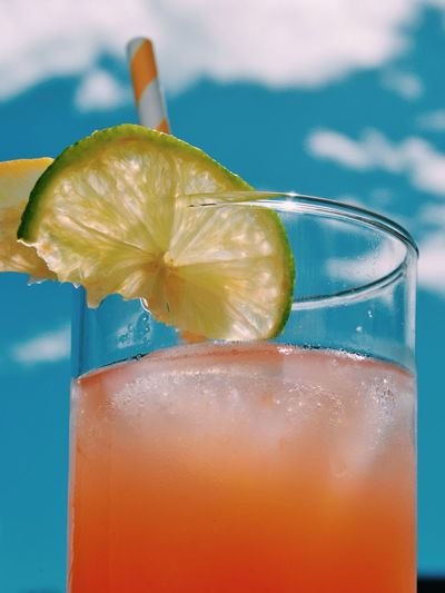 Close-up of cocktail served in glass against sky