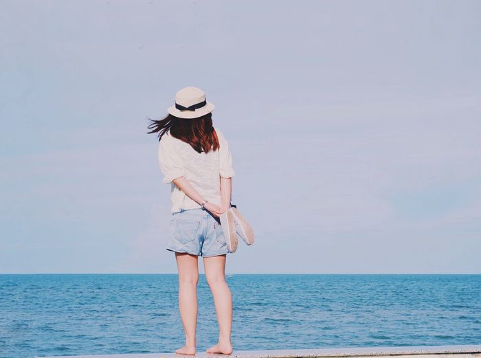 Sea Horizon Over Water Water Hat One Person Real People Scenics Nature Standing Outdoors Leisure Activity Lifestyles Rear View Beauty In Nature Full Length Beach Day Sky Sun Hat Vacations Young Women Summer Summertime Fashion Tourism