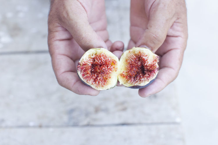 Close-up of hands holding fig slices