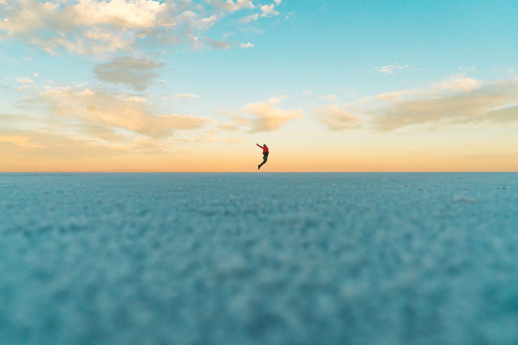 Surface level of man jumping over salt flat against sky during sunset