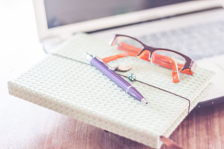 Close-up of eyeglasses with pen and diary on laptop over table