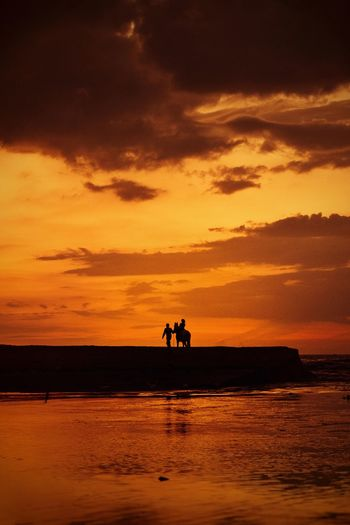 Silhouette people riding on sea against sky during sunset