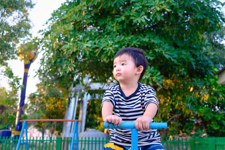 Boy looking away while sitting on seesaw in park against trees