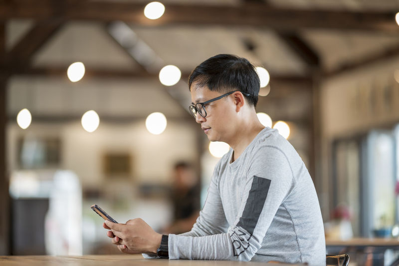 Side view of man using mobile phone sitting at cafe