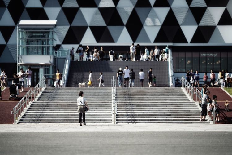 People walking on staircase in city