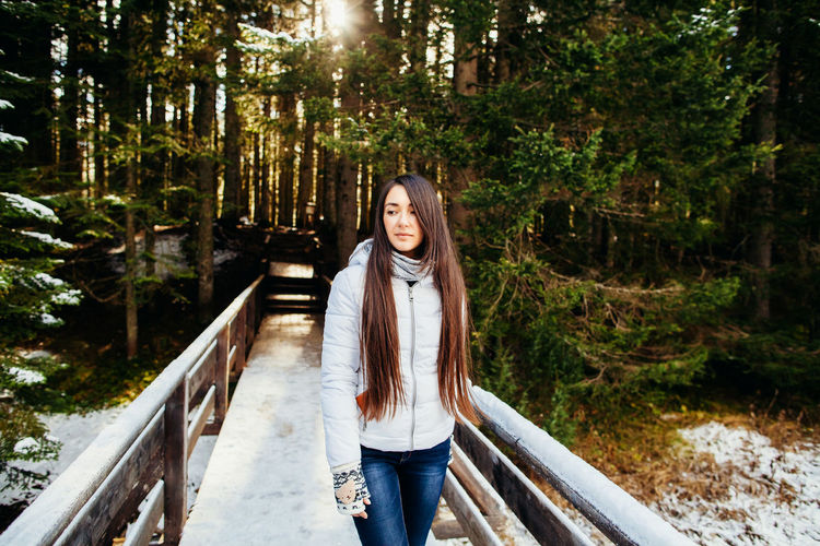 Woman Standing On Snowy Footbridge In Forest