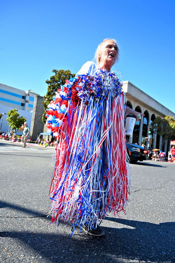 This woman was selling flag colors in the street during the Independence day parade at downtown Modesto, California Real People Women City Sunlight Street One Person Architecture Sky Clear Sky Day Adult Lifestyles Incidental People Blond Hair Road Building Exterior Transportation Nature Outdoors 4th Of July Streetphotography