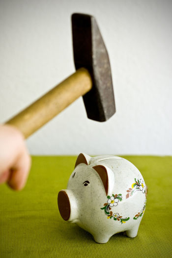 Close-up of person holding hammer over piggy bank