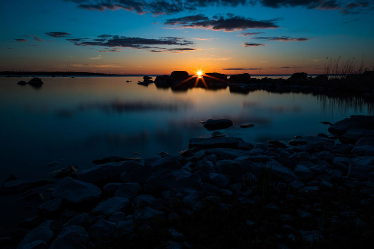 Beauty In Nature Bluehour Nature Outdoors Reflection Silhouette Sky Sunburst Sunset Sunset #sun #clouds #skylovers #sky #nature #beautifulinnature #naturalbeauty #photography #landscape Sunset And Clouds  Sunset Silhouettes Sunset_captures Sunset_collection Sunsetlover Sunsetphotographs Sunsetporn Sunsets Water