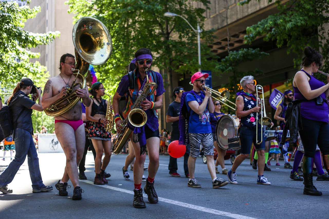 musical instrument, music, musician, large group of people, real people, day, outdoors, performance, leisure activity, street, arts culture and entertainment, playing, fun, street performer, full length, togetherness, men, building exterior, happiness, performance group, adult, people