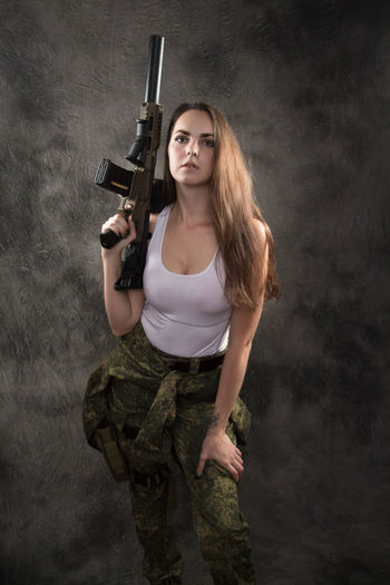 Adult Aggression  Beautiful Woman Beauty Communication Gun Hair Hairstyle Handgun Holding Long Hair Looking At Camera Machine Gun One Person Portrait Protection Sign Standing Warning Sign Weapon Young Adult Young Women