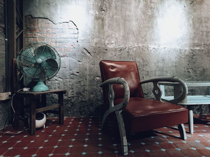 Empty armchair by electric fan in old room