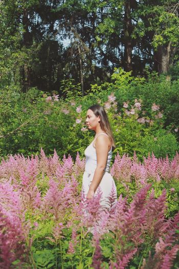 Side View Of Woman Standing Amidst Flowers At Park