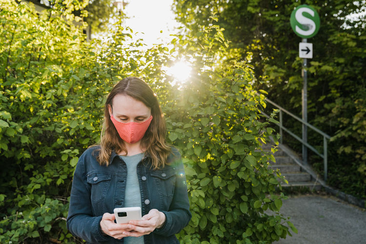 Young woman using phone while standing by plants