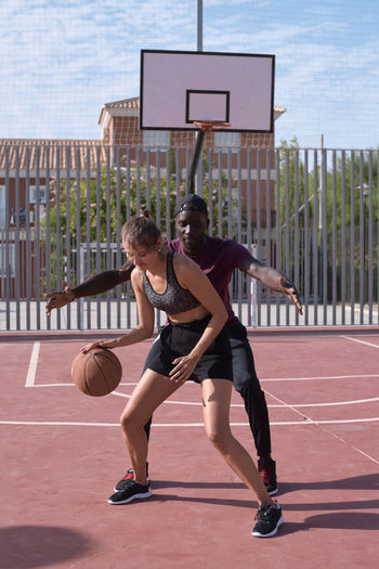 Full length of young woman playing basketball