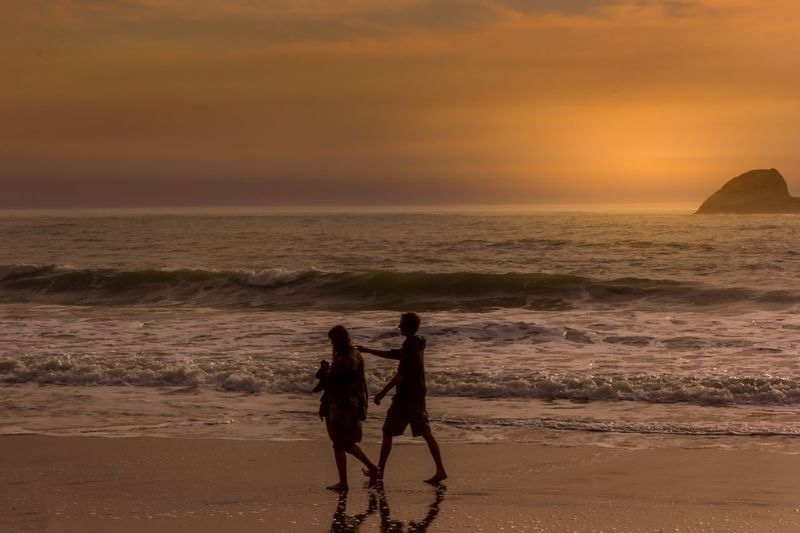 Couple walking on shore at beach against sea during sunset