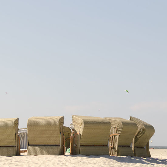 Hooded chairs on beach against clear sky