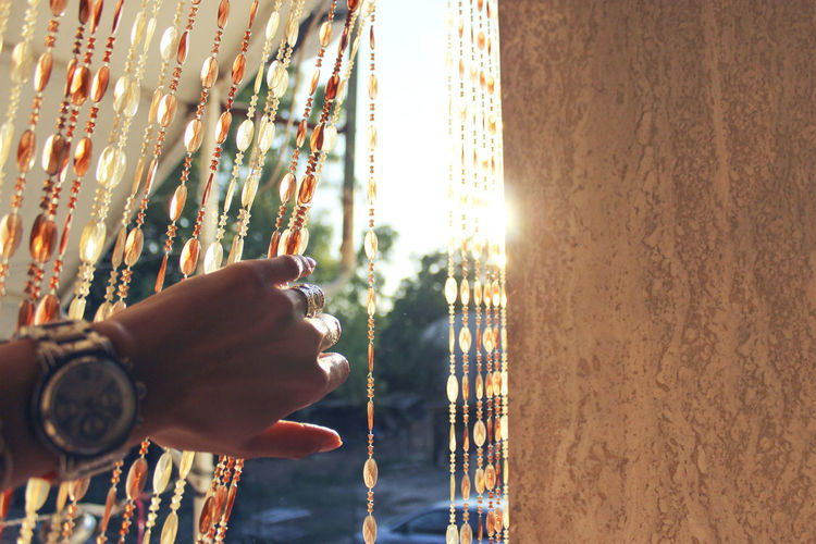 Hand of woman holding beaded curtain by wall