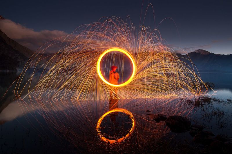 Light painting by lake against sky at night