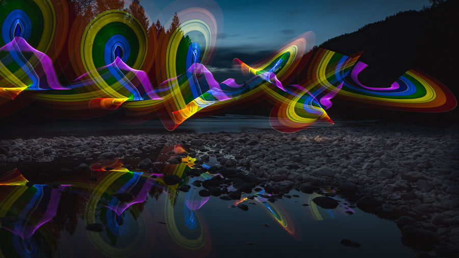 Multi colored illuminated rainbow over water at night