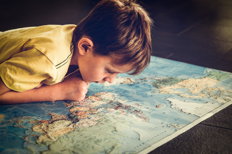 Close-Up Of Boy Looking Into Map