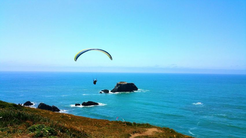 The jump off the cliff ! Paragliding over the ocean. Dangerous Extreme Sports Thrill Background Copy Space Zen Blue Sky Fog Timeless Moment Paragliding Extreme Sports Parachute Sea Water Adventure Sport Flying RISK Sky Gliding Seascape Ocean Coast Tranquil Scene Horizon Over Water Countryside Idyllic Tranquility Calm