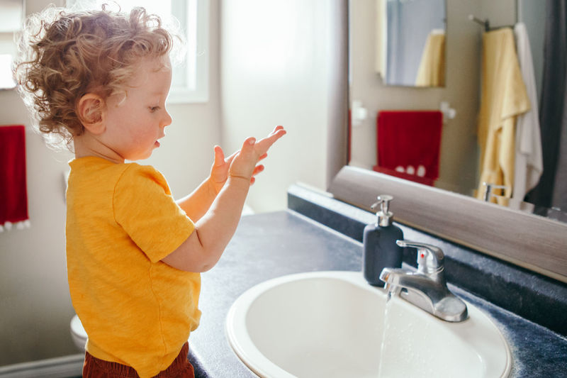 boy toddler washing hands in bathroom at home. health hygiene and morning routine for children.