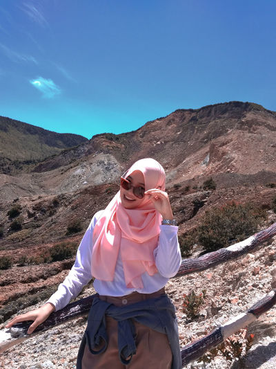 Portrait of woman in hijab standing against mountain