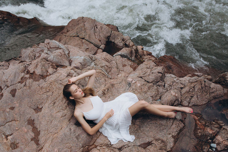 High angle view of woman relaxing on cliff by sea