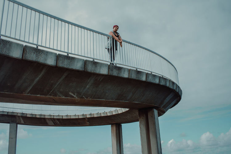 Low angle view of man standing on bridge against sky