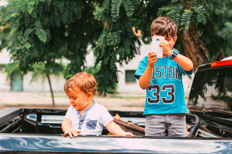 Boy and son while sitting on car outdoors