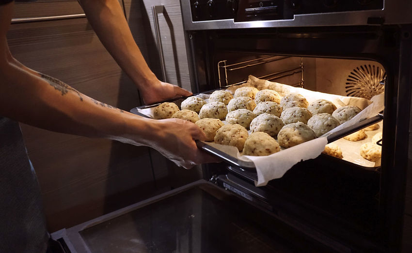 Cropped image of man putting tray into oven