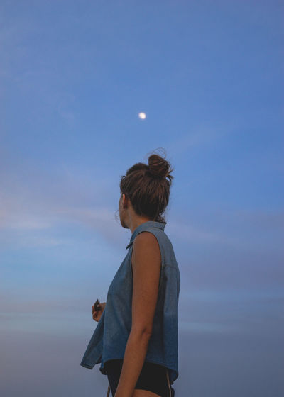 Side view of woman standing against sky during dusk