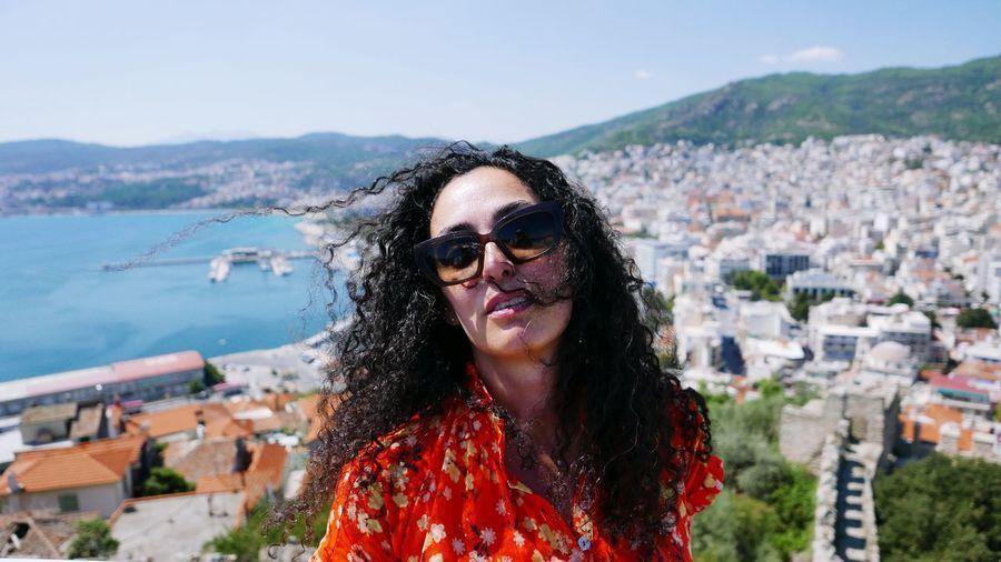 Portrait of woman wearing sunglasses against city